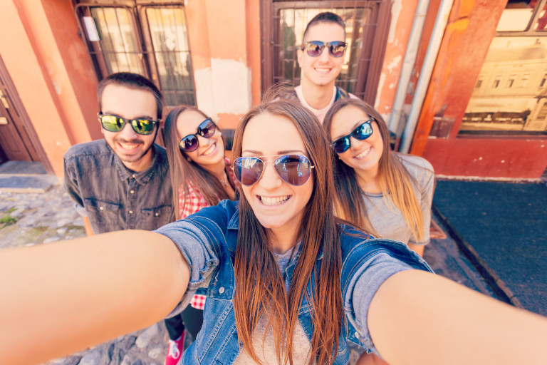 Friendship and summer holidays concept. Group of teenagers having good fun on the city streets making a selfie.